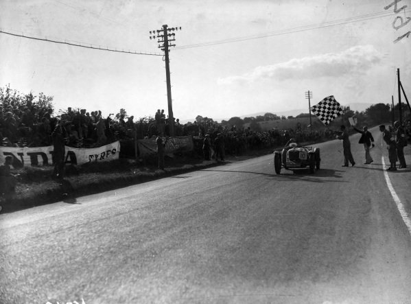 Freddie Dixon, Riley TT Sprite, crosses the line and takes the chequered flag.