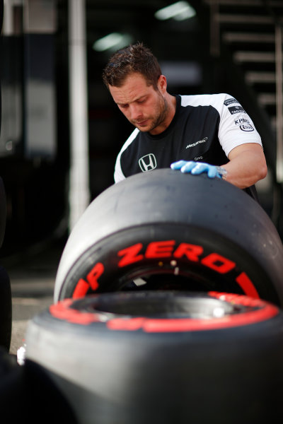 Red Bull Ring, Spielberg, Austria. Friday 19 June 2015. A McLaren employee works on tyres. World Copyright: Alastair Staley/LAT Photographic. ref: Digital Image _R6T0860