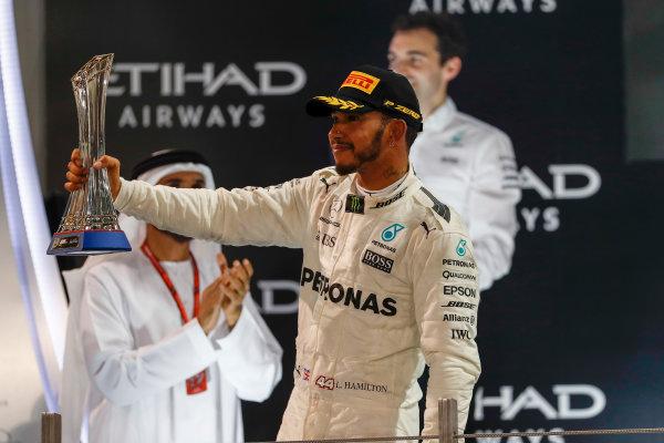 Yas Marina Circuit, Abu Dhabi, United Arab Emirates. Sunday 26 November 2017. Lewis Hamilton, Mercedes AMG, with his trophy on the podium. World Copyright: Glenn Dunbar/LAT Images  ref: Digital Image _X4I9815