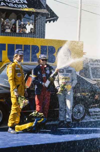 Niki Lauda celebrates victory on the podium with Riccardo Patrese, 2nd position, and Ronnie Peterson, 3rd position.