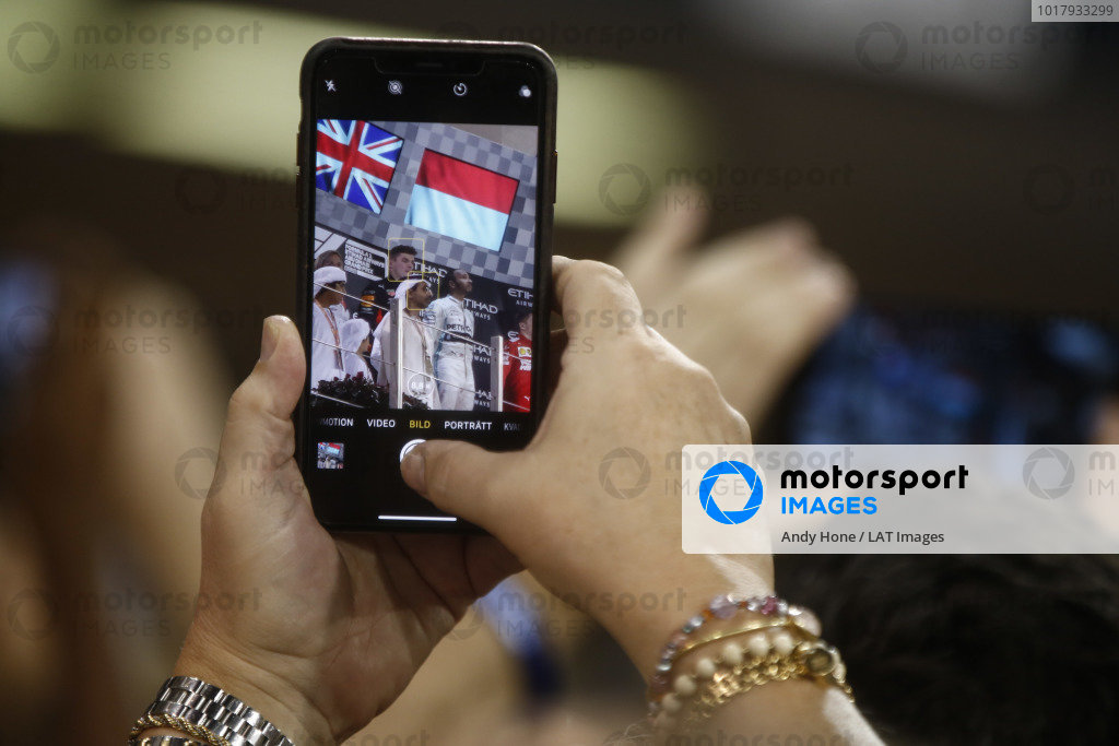 bmp, 2nd position, and Lewis Hamilton, Mercedes AMG F1, 1st position, on the podium, as seen through a phone screen