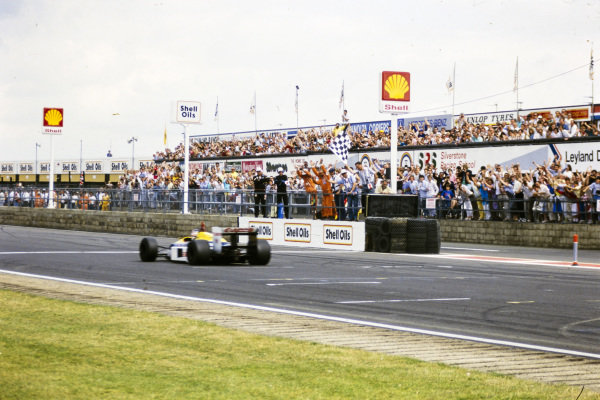 Nigel Mansell, Williams FW11B Honda, celebrates as he takes the chequered flag.
