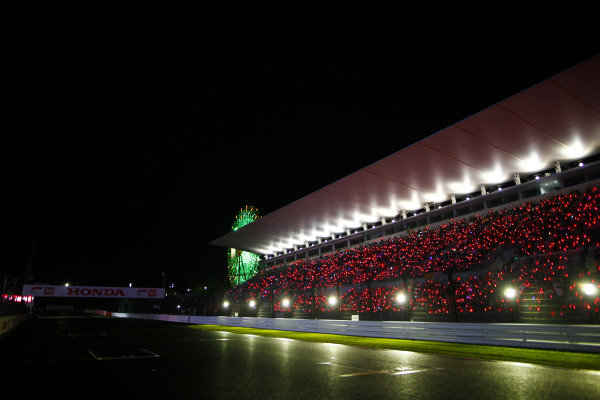 Fans in the pit straight grandstand wave glow sticks and torches.