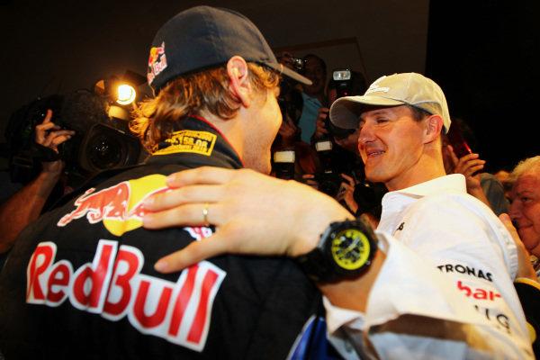 Michael Schumacher (GER) Mercedes GP congratulates 2010 World Champion Sebastian Vettel (GER) Red Bull Racing. Formula One World Championship, Rd 19, Abu Dhabi Grand Prix, Race, Yas Marina Circuit, Abu Dhabi, UAE, Sunday 14 November 2010.
