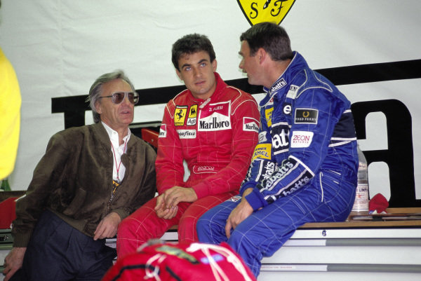 Bernie Ecclestone, Jean Alesi, Ferrari, and Nigel Mansell, Williams, talk in the Ferrari garage.