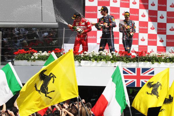 The podium (L to R): Fernando Alonso (ESP) Ferrari, Mark Webber (AUS) Red Bull Racing and Sebastian Vettel (GER) Red Bull Racing spray the champagne. Formula One World Championship, Rd 9, British Grand Prix, Race, Silverstone, England, Sunday 10 July 2011.  BEST IMAGE