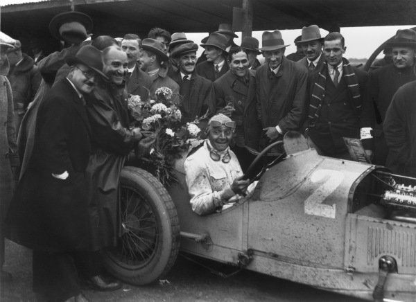 Brooklands, Great Britain. 1st October 1927. Robert Benoist (Delage 15S8), 1st position. Reserve driver Robert Senechal is holding flowers on the left of the car, portrait, podium. World Copyright: LAT Photographic.  Ref:  Autocar Glass Plate A8711.