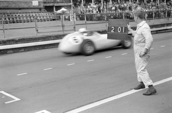 A mechanic holds out a pit board for Stirling Moss in his BRM P25.