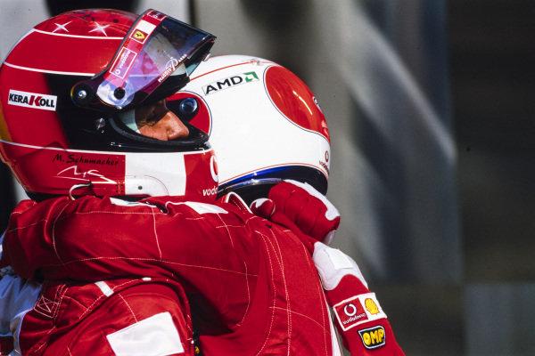 Rubens Barrichello hugs Michael Schumacher in Parc Ferme.
