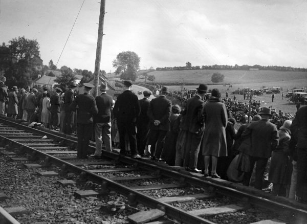Fans stand on the railway bridge to get a good vantage point.