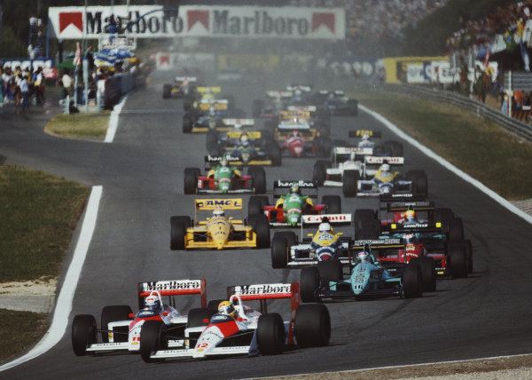 Ayrton Senna, McLaren MP4-4 Honda, ahead of team-mate Alain Prost, Ivan Capelli, March 881 Judd, Gerhard Berger, Ferrari F1/87/88C and the rest of the pack at the start.