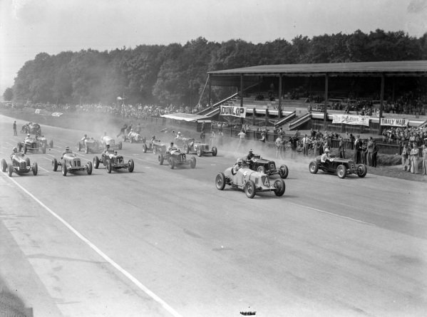 """B Bira"", Maserati 8CM, leads the field away at the start, with Arthur Dobson, ERA-C (#9), and Raymond Mays, ERA-B (#8), while Austin Dobson, Maserati 6CM (#18), Earl Howe, ERA-B (#10), Charles Martin, ERA-A (#12), and Peter Whitehead, ERA-B (#15), are all side by side behind."