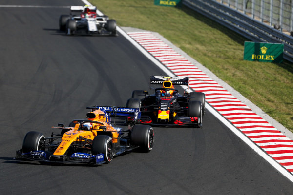 Carlos Sainz Jr., McLaren MCL34, leads Pierre Gasly, Red Bull Racing RB15, and Antonio Giovinazzi, Alfa Romeo Racing C38