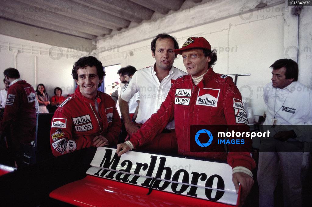 Alain Prost, Ron Dennis and Niki Lauda in the McLaren garage with Hans Mezger behind.