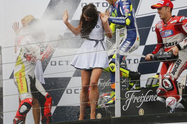 2015 MotoGP Championship.  British Grand Prix.  Silverstone, England. 28th - 30th August 2015.  Danilo Petrucci, Pramac Ducati, 2nd position, Valentino Rossi, Yamaha, 1st position, and Andrea Dovizioso, Ducati, 3rd position, celebrate on the podium.  Ref: KW5_5596a. World copyright: Kevin Wood/LAT Photographic