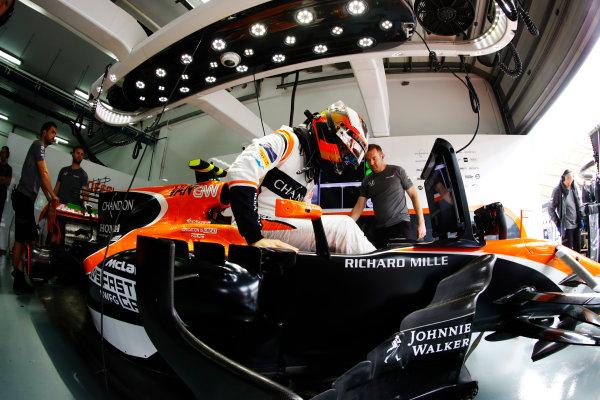 Sepang International Circuit, Sepang, Malaysia. Friday 29 September 2017. Stoffel Vandoorne, McLaren, enters his cockpit in the team's garage. World Copyright: Steven Tee/LAT Images  ref: Digital Image _R3I2806