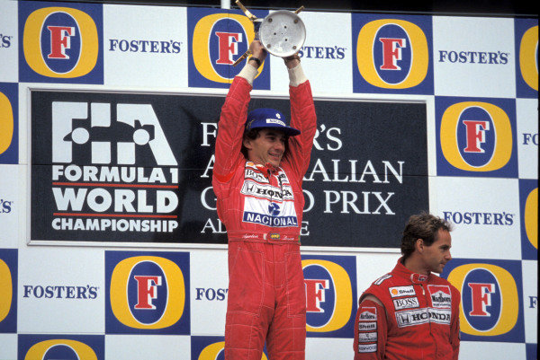 Ayrton Senna, 1st position, lifts his trophy as Gerhard Berger, 3rd position, looks on.