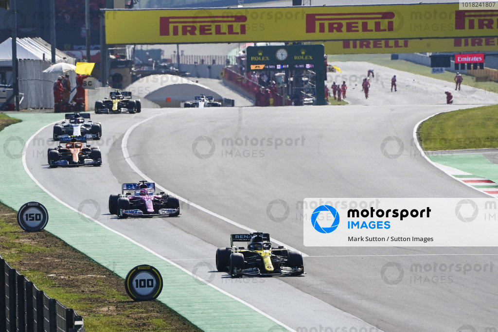 Daniel Ricciardo, Renault R.S.20, leads Sergio Perez, Racing Point RP20, Lando Norris, McLaren MCL35, and the remainder of the field out of the pits for the restart