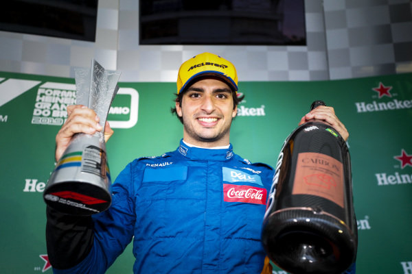 Carlos Sainz Jr, McLaren on the podium with the trophy an the champagne