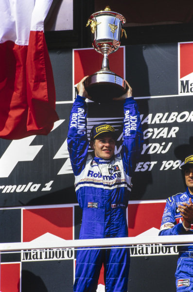 Jacques Villeneuve, 1st position, celebrates on the podium with his trophy.