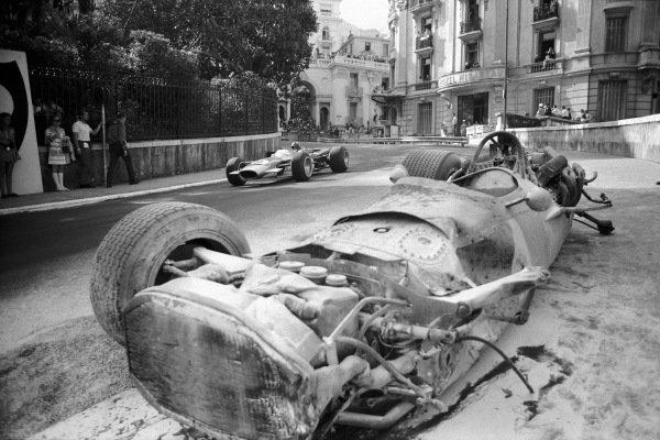 Graham Hill, Lotus 49B Ford passes Pedro Rodriguez' destroyed BRM P133.
