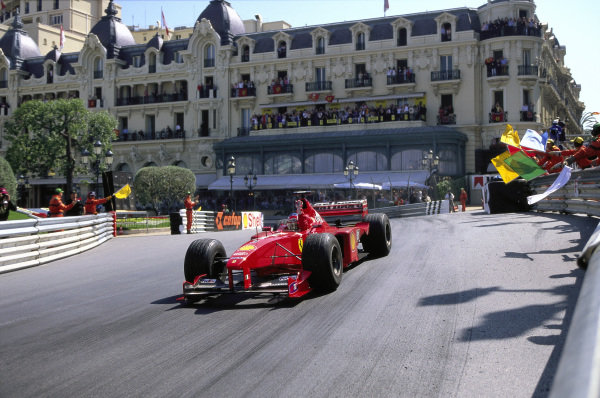 Michael Schumacher, Ferrari F399, celebrates victory as he comes through Casino Square with marshals waving their flags.