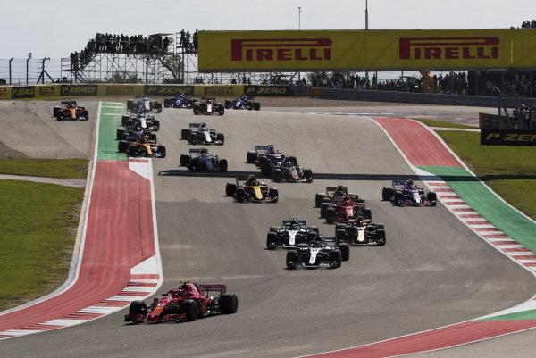 Kimi Raikkonen, Ferrari SF71H, leads Lewis Hamilton, Mercedes AMG F1 W09 EQ Power+, Valtteri Bottas, Mercedes AMG F1 W09 EQ Power+, Daniel Ricciardo, Red Bull Racing RB14, Sebastian Vettel, Ferrari SF71H, and the rest of the field on the opening lap