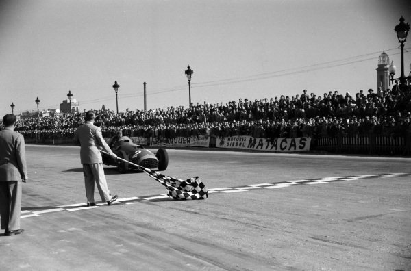 Alberto Ascari, Ferrari 375, takes the chequered flag for fourth position.