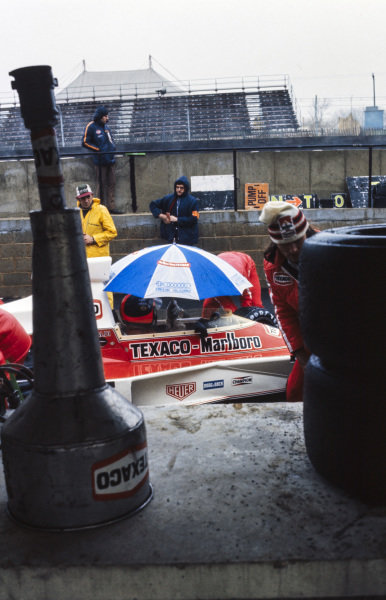 Emerson Fittipaldi, McLaren M23 Ford keeps dry in the pit lane.