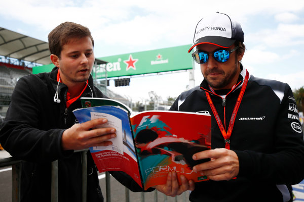 Autodromo Hermanos Rodriguez, Mexico City, Mexico. Thursday 27 October 2016. Fernando Alonso, McLaren, signs an autograph with a fa, World Copyright: Andy Hone/LAT Photographic ref: Digital Image _ONZ0077