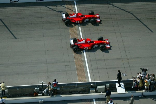 Rubens Barrichello (BRA, below) Ferrari F2002 inches past team mate Michael Schumacher (GER) Ferrari F2002 to take an unexpected victory.