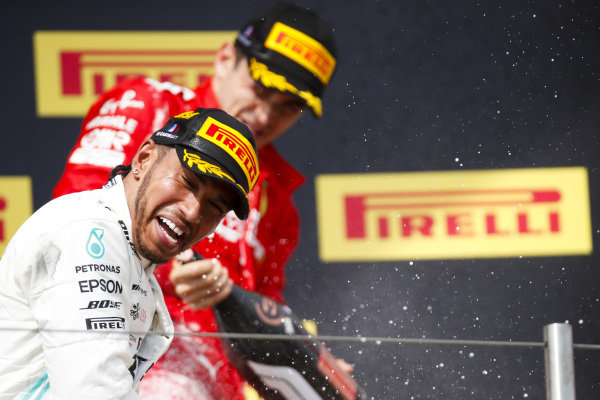 Lewis Hamilton, Mercedes AMG F1, 1st position, and Charles Leclerc, Ferrari, 3rd position, spray Champagne on the podium