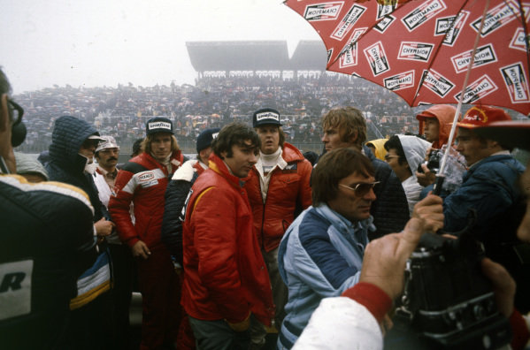 James Hunt, Niki Laura, Ronnie Peterson, Jean-Pierre Jarier, Max Mosley and Bernie Ecclestone attend the drivers' briefing in the pouring rain.