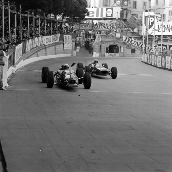 Phil Hill, Lotus 25 Climax, with a camera mounted to the front recording on board footage for the 'Grand Prix' movie. He signals for Bob Anderson, Brabham BT11 Climax, to pass by.