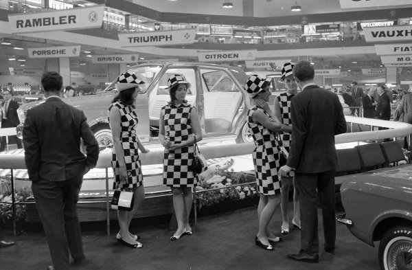 Models wearing chequer pattern outfits in front of a MkII Ford Cortina display.