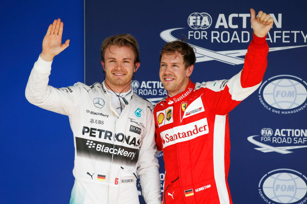 Interlagos, Sao Paulo, Brazil. Saturday 14 November 2015. Nico Rosberg, Mercedes F1 W06 Hybrid and Sebastian Vettel, Ferrari celebrate after qualifying. World Copyright: Glenn Dunbar/LAT Photographic. ref: Digital Image _W2Q5208