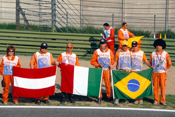 2004 San Marino Grand Prix.Imola, Italy. 23rd - 25th April 2004.The marshals hold the Brazil and Austrian flags in a mark of respect to Ayrton Senna and Roland Ratzenberger.World Copyright: Charles Coates/LAT Photographic.Ref: 35mm Image A28