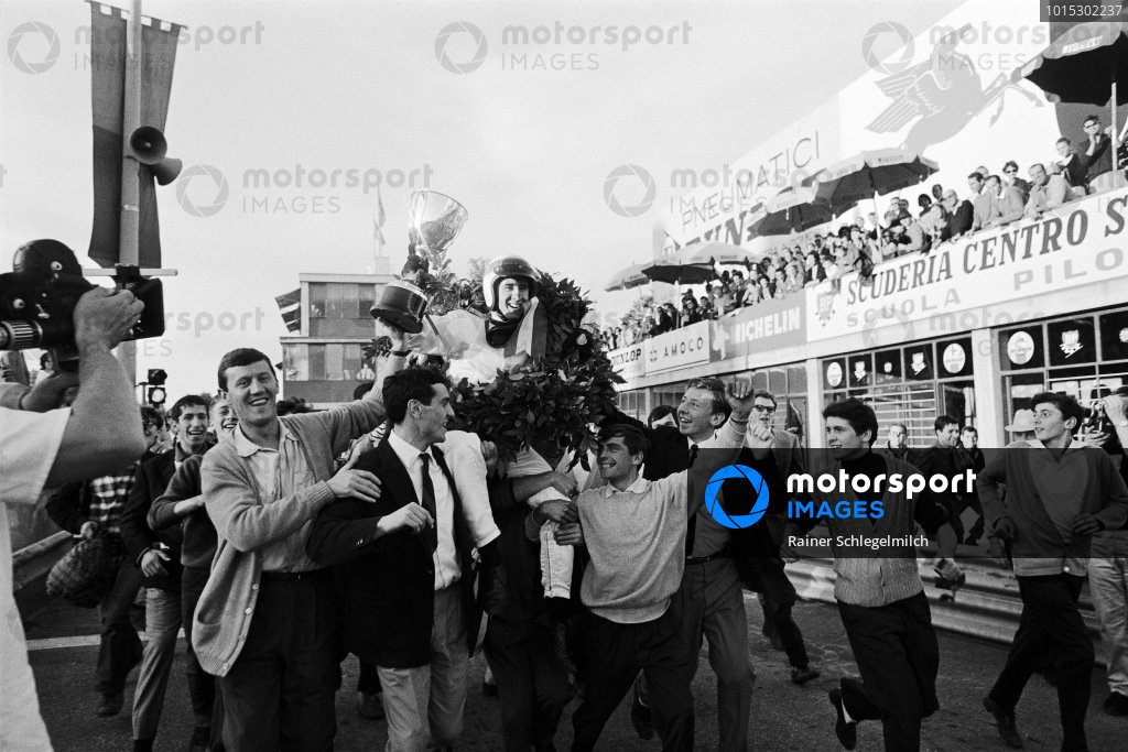 Race winner Jackie Stewart carried by cheering fans after his first Grand Prix victory.