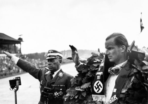 1938 German Grand Prix.  Nurburgring, Germany. 24 July 1938.  Dick Seaman, Mercedes-Benz W154, 1st position, gives a half-hearted Nazi salute on the podium next to Major Adolf Huhnlein.  Ref: RF38_GER_03. World Copyright: Robert Fellowes/LAT Photographic