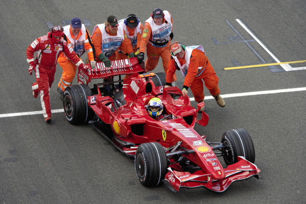 After stalling on the grid, marshals push Felipe Massa in his Ferrari F2007 to the pits for a pitlane start.