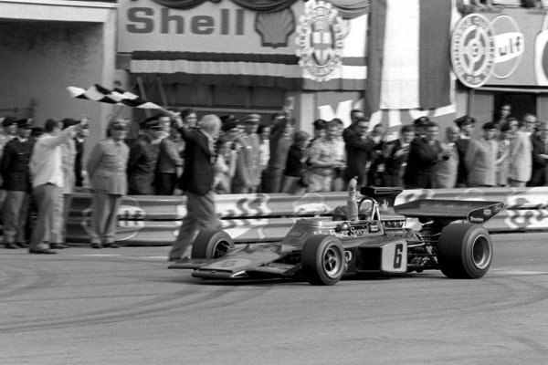 Emerson Fittipaldi, Lotus 72D Ford, celebrates victory and becoming world champion as he takes the chequered flag.