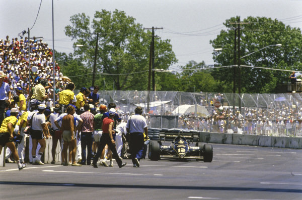 Nigel Mansell is attended to beside his Lotus 95T Renault, after fainting while attempting to push his car across the finish line having run out of fuel at the end of the race.