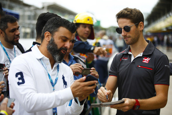Romain Grosjean, Haas F1 Team, signs autographs for fans.
