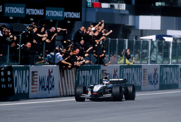 2003 Malaysian Grand Prix Sepang, Malaysia. 21st - 23rd March 2003. Race winner Kimi Raikkonen, Team McLaren Mercedes MP4-17D, crosses the finish line to the cheers of the McLaren team. World Copyright: Charles Coates / LAT Photographic  ref: 35mm Image A28