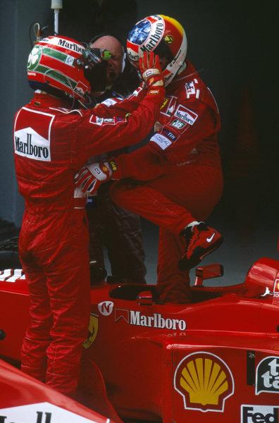 Sepang, Kuala Lumpur, Malaysia. 15-17 October 1999. In parc ferme Eddie Irvine thanks Ferrari teammate Michael Schumacher for helping him to win.  Ref: 99MAL15. World Copyright - LAT Photographic
