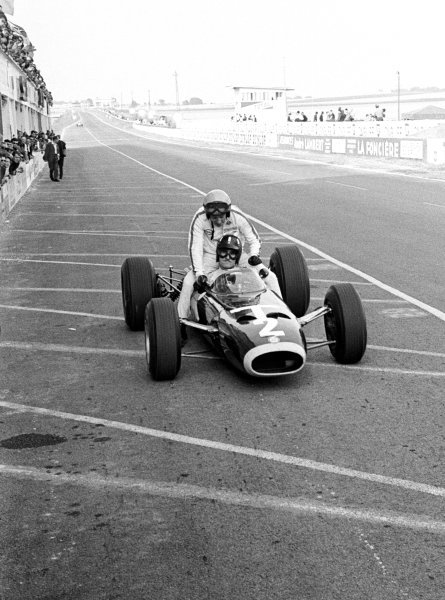 Race retiree Graham Hill (GBR) BRM P261 gives fellow retiree Peter Arundell (GBR) a lift back to the pits. French Grand Prix, Reims, 3 July 1966.