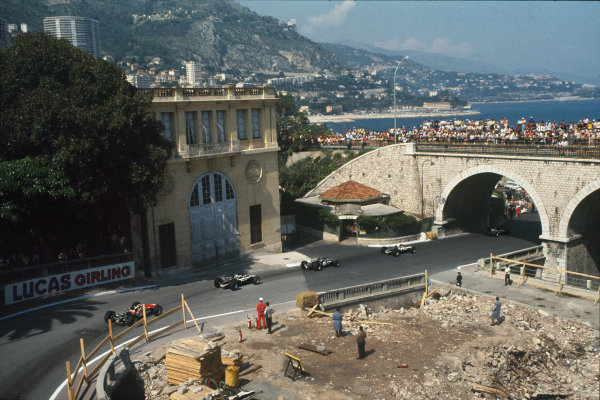 Monte Carlo, Monaco. 23-26 May 1968.  Denny Hulme (McLaren M7A-Ford Cosworth) leads Ludovico Scarfiotti (Cooper T86B-BRM), Dan Gurney (Eagle T1G-Weslake), Lucien Bianchi (Cooper T86B-BRM) and Jackie Oliver (Lotus 49-Ford Cosworth) into Le Portier.  Ref: 68MON12. World Copyright: LAT Photographic