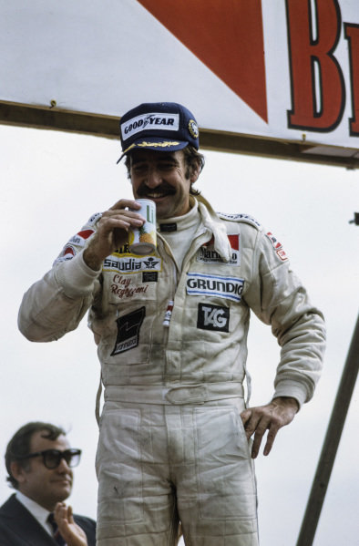 Clay Regazzoni celebrates victory on the podium with a soft drink.