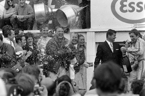 Dan Gurney, 1st position, and 2.0 class winnerJo Siffert spray Champagne on the podium.