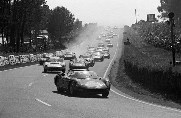 John Surtees / Lorenzo Bandini, Scuderia Ferrari, Ferrari 330P, leads Claude Dubois / Keith Ballisat, Rootes Group, Sunbeam Tiger, Jean Guichet / Nino Vaccarella, Scuderia Ferrari, Ferrari 275P, and the rest of the field on the opening lap.
